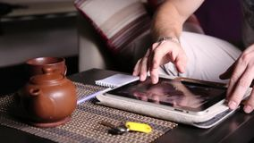 Jonge zakenman gebruikend tabletcomputer voor online het winkelen en makend nota's in een notitieboekje Mens die aan PC-tablet we stock footage