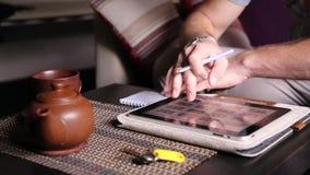 Jonge zakenman gebruikend tabletcomputer voor online het winkelen en makend nota's in een notitieboekje Mens die aan PC-tablet we stock video