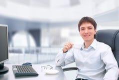 Jonge zakenman in glazen die op zijn kantoor werken. Stock Fotografie