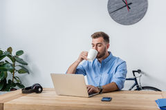 Jonge zakenman het drinken koffie terwijl het werken in bureau Royalty-vrije Stock Afbeeldingen