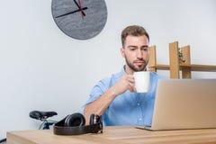 Jonge zakenman het drinken koffie terwijl het werken met laptop in bureau Stock Afbeelding