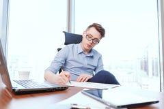 Jonge zakenman het vullen documenten in bureau royalty-vrije stock afbeelding