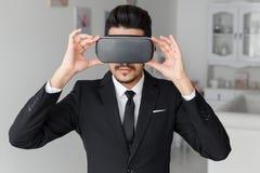 Jonge zakenman in kostuum en virtuele glazen Stock Fotografie