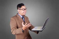 Jonge Zakenman Looking bij Laptop, het Glimlachen Uitdrukking stock afbeeldingen