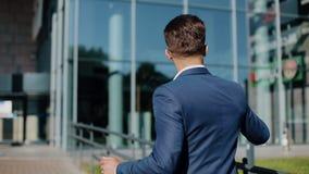 Jonge zakenman met aan de muziek op zijn smartphone luisteren in openlucht en zonnebril die dansen Hij die dichtbij bureau lopen stock videobeelden