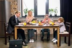 jonge zakenman met familie die ontbijt hebben en digitale apparaten met behulp van royalty-vrije stock afbeelding