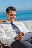 Jonge zakenman op een ligstoel die zijn tablet gebruiken stock fotografie