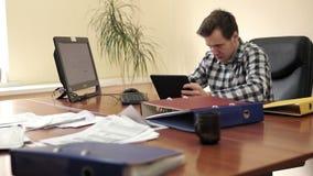 Jonge zakenman op zijn kantoor stock footage