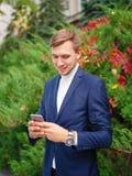 Jonge zakenman in openlucht met telefoon in handen royalty-vrije stock foto