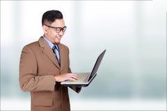 Jonge Zakenman Smiling Looking bij Laptop royalty-vrije stock fotografie