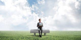 Jonge zakenman of student die de wetenschap in de zomerpark bestuderen Stock Foto's