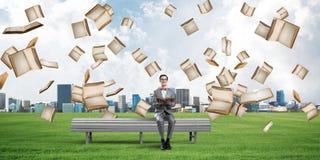 Jonge zakenman of student die de wetenschap in de zomerpark bestuderen Stock Afbeeldingen