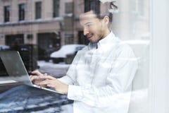 Jonge zakenman of studentenzitting en het werken aan de vensterbank met open laptop aan knieën Royalty-vrije Stock Foto's