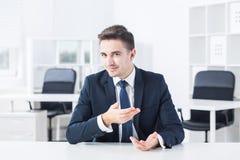 Jonge zakenman tegengesteld aan zijn werkgever royalty-vrije stock foto's