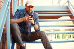 Jonge zakenmanberoeps die op smartphone in straat lopen die app texting sms bericht op smartphone gebruiken royalty-vrije stock fotografie