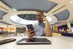Jonge Zakenmanplaatsing op lijst in restoran en gebruik mobiel DE Stock Foto