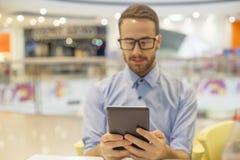 Jonge Zakenmanplaatsing op lijst in restoran en gebruik mobiel DE Stock Afbeeldingen