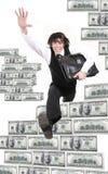 Jonge zakenmansprongen door dollars Royalty-vrije Stock Foto