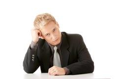 Jonge zakenmanzitting achter het bureau Stock Afbeelding