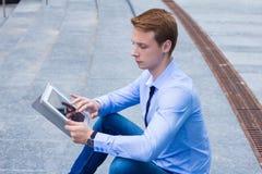 Jonge zakenmanzitting in de straat dichtbij het commerciële centrum en de werkzaamheden aangaande de tablet royalty-vrije stock foto