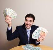 Jonge zakenmanzitting in een kostuum achter een bureau Royalty-vrije Stock Afbeeldingen