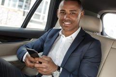 Jonge zakenmanzitting op achterbank in auto die smartphone gebruiken die camera gelukkig close-up kijken royalty-vrije stock fotografie