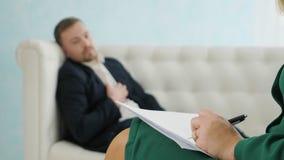 Jonge zakenmanzitting op bank die aan zijn therapeut bij therapiezitting spreken stock footage