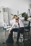 Jonge zakenmanzitting op stoel en het drinken whisky van fles in bureau stock fotografie