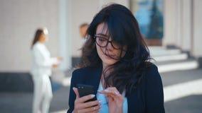 Jonge zakenvrouw in Eyeglassen die in de stad staat met Smartphone in haar handen Het kijken gelukkig en Tevreden Kantoor stock video