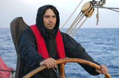 Jonge zeeman die lang schip sturen stock afbeeldingen
