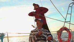 Jonge zeeman en hogere kapitein op zeilboot, groepswerk, hulp stock video