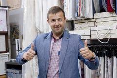 Jonge zekere positieve de opslageigenaar die van de zakenmanstof duimen tonen, gebaarteken o.k. Mens die zich op de opslagachterg royalty-vrije stock afbeelding