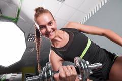 Jonge zekere vrouw die de oefening van de bicepsenkrul met domoren in geschiktheidscentrum doen Slanke meisje opleiding in de gym Royalty-vrije Stock Foto's