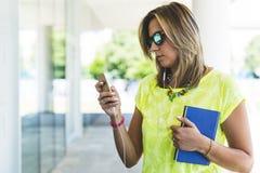 Jonge zekere vrouw die in openlucht en met smar haar texting werken Royalty-vrije Stock Foto's