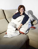 Jonge zieke die vrouwenzitting op laag in dekbed wordt verpakt en deken die miserabel voelen Stock Afbeeldingen