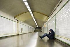 Jonge zieke verloren mens het lijden van depressie aan zitting op de metrotunnel van de grondstraat Stock Foto
