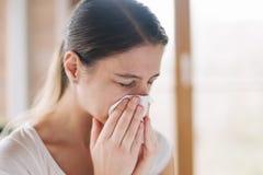 Jonge zieke vrouw die haar neus blazen bij een heldere zonnige scène royalty-vrije stock fotografie
