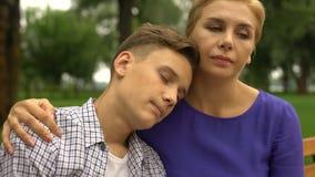 Jonge zoon die in wanhoop hoofd op moedersschouder zetten die kalmte en liefde voelen stock video