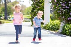 Jonge Zuster en Broer Having Fun Running bij het Park stock afbeeldingen