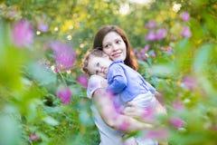 Jonge zwangere moeder die haar vermoeide babydochter houden Stock Afbeelding