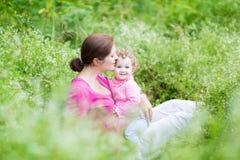 Jonge zwangere moeder en haar babydochter in tuin royalty-vrije stock foto's