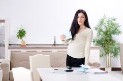 Jonge zwangere vrouw in begroting planningsconcept stock foto