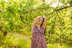 Jonge zwangere vrouw in bloeiende tuin Royalty-vrije Stock Afbeelding