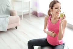 Jonge zwangere vrouw die appel eten royalty-vrije stock fotografie