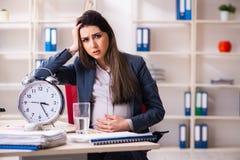 Jonge zwangere vrouw die in het bureau werken royalty-vrije stock fotografie
