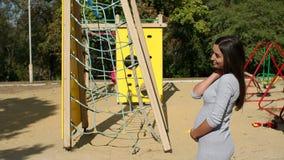 Jonge zwangere vrouw die in het Park dichtbij de Speelplaats lopen stock video