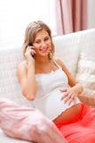 Jonge zwangere vrouw die mobiele telefoon spreekt Stock Foto's