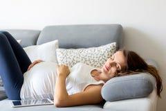 Jonge zwangere vrouw, die op laag in woonkamer, relaxi liggen stock afbeeldingen