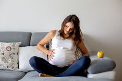 Jonge zwangere vrouw, die pijnlijke samentrekking hebben, die arbeid beginnen stock foto's