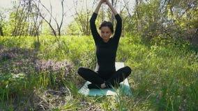 Jonge zwangere vrouw die yoga buiten doen stock videobeelden